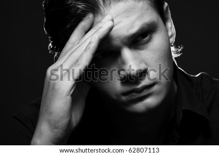 Closeup portrait of a upset young man with hand on his head