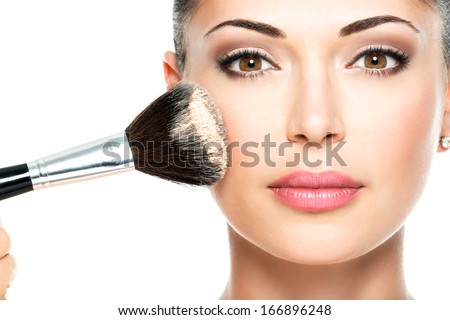 Closeup portrait of a woman  applying dry cosmetic tonal foundation  on the face using makeup brush.  #166896248