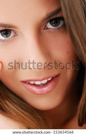 Closeup portrait of a woman who is touching her face