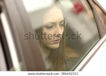 Closeup portrait of a worried car passenger looking at side through the window in a sad rainy day