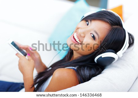 Closeup portrait of a young asian woman in headphones listening to music with her smartphone
