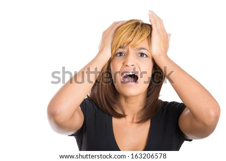 Closeup portrait of a young, attractive stressed woman who is going crazy putting hands on head yelling in frustration, isolated on a white background. Negative human emotions facial expressions.