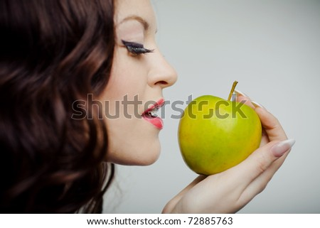 Closeup portrait of a young beautiful girl making a bite on green apple standing on half-face