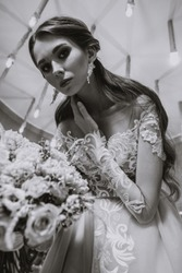 Closeup portrait of a young beautiful woman bride in a beige flesh-colored dress with lace. Interior with lots of lamps, restaurant, vintage armchairs and chairs, dramatic light, fashion style. Long