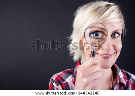 Closeup portrait of a young blond woman with magnifying glass against black background
