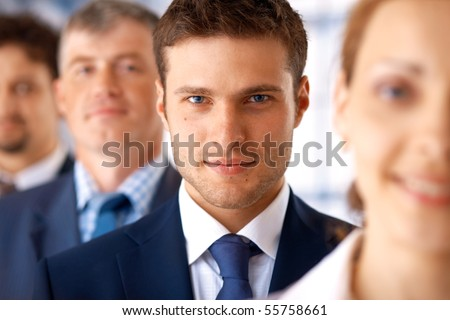 Closeup portrait of a young businessman standing in the row with his colleagues.