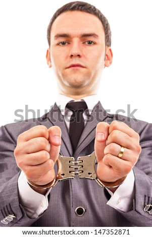 Closeup portrait of a young businessman with handcuffed hands. White background