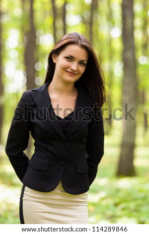 Closeup portrait of a young businesswoman standing in the woods