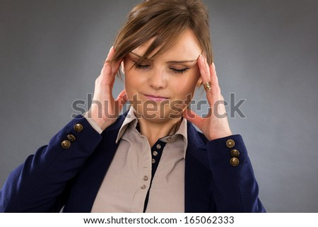 Closeup portrait of a young businesswoman with headache isolated on gray background