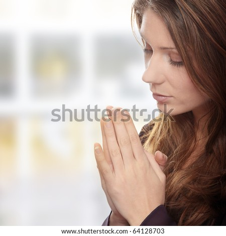Closeup portrait of a young caucasian woman praying
