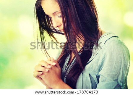 Closeup portrait of a young caucasian woman praying, against abstract green background