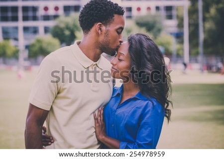 Closeup portrait of a young couple, guy holding woman and kissing face, happy moments, positive human emotions on isolated outdoors outside park background. Retro faded vintage look