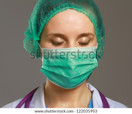 Closeup portrait of a young doctor wearing a mask isolated on grey background