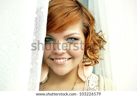 Closeup portrait of a young happy ginger haired girl