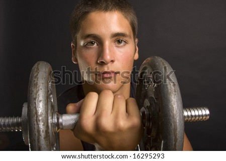 Closeup portrait of a young man lifting weights as framed in a dumbbell.