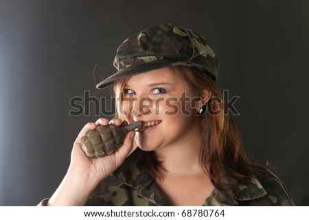 Closeup portrait of a young pretty female model holding the pin of mockup airsoft F-1 grenade in her teeth in studio