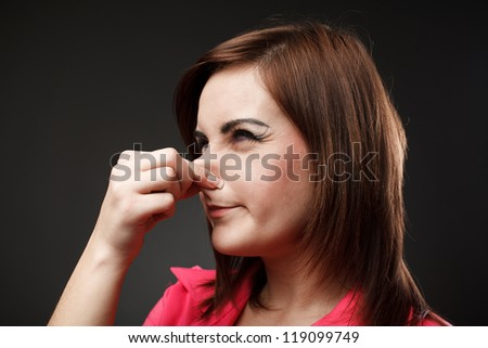 Closeup portrait of a young woman holding her nose because of a bad smell