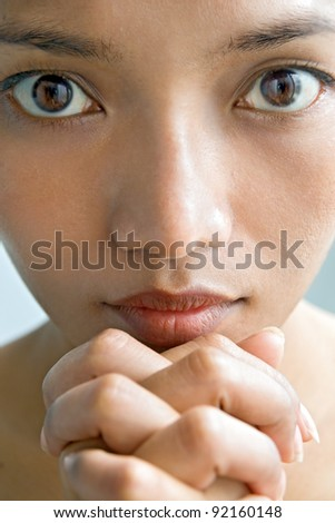 Closeup portrait of a young woman praying