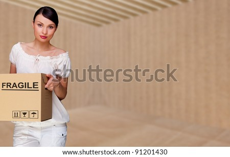 Closeup portrait of a young woman with boxes moving to her new home. Empty home packed into box. Everything is ready to move