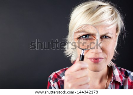 Closeup portrait of a young woman with magnifying glass against black background