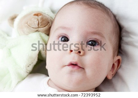 closeup portrait of adorable baby with toy - stock photo