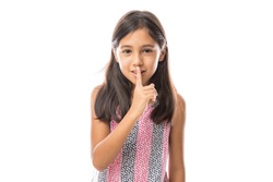 Closeup portrait of adorable blonde girl putting finger up to lips and saying shh, isolated on white background