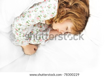 Closeup portrait of adorable little girl resting in her bed with white linen