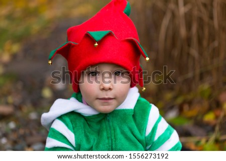 Closeup portrait of adorable small boy in elf suit and hat with cute innocent expression in outdoors location #1556273192