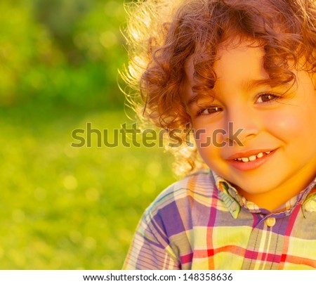 Closeup portrait of adorable sweet child on summer field, nice little boy with curly hair having fun on backyard, happiness and joy concept
