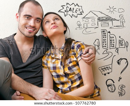 Closeup portrait of adult couple sitting on floor at their apartment and planning renovation of their new apartment while resting during housework