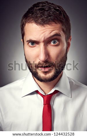 closeup portrait of amazed man over grey background