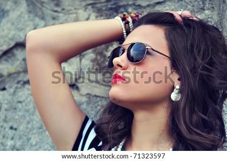 Closeup portrait of an attractive brunette girl wearing sunglasses