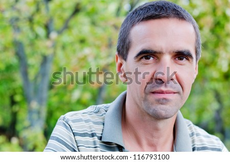 Closeup portrait of an attractive serious middle-aged man looking directly into the camera standing outdoors amongst trees with copyspace