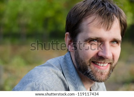 Closeup portrait of an attractive serious middle-aged man standing outdoors amongst trees with copyspace