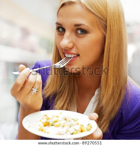 Closeup portrait of an attractive young woman eating fruit salad at cafe inside shopping mall or airport