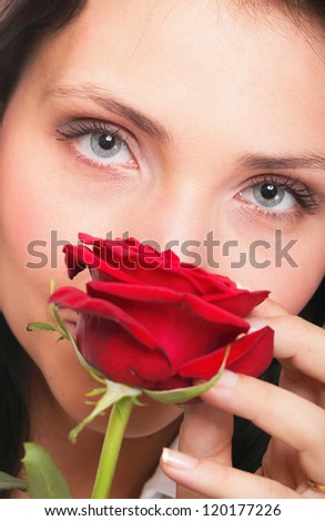 Closeup portrait of an attractive young woman holding a red rose