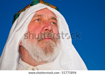 Closeup Portrait of an Older Arab Man Isolated against Blue Sky.