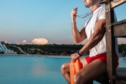 Closeup portrait of an unrecognizable lifeguard with a whistle in his hands. Copy space. Lifeguards at the resort.