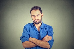 Closeup portrait of angry grumpy young man looking very displeased isolated on gray wall background. Negative human emotions facial expression feelings attitude
