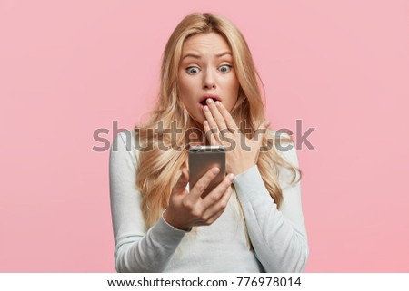 Closeup portrait of anxious scared young girl looking at phone seeing bad news or photos isolated over pink background. Negative emotions. Human reaction, expression and technology concept