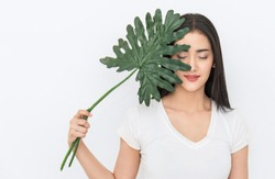 Closeup portrait of attractive asian woman has green leaf cover face with perfect healthy glow skin, asian beautiful girl. Beauty clinic cosmetology skincare organic green natural earth day concept