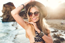Closeup portrait of attractive blonde girl with long hair posing on rocky beach on sunset background. She wears bikini, hat, sunglasses. She is smiling.