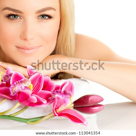 Closeup portrait of attractive female in spa with pink orchid flower, pretty woman with luxury natural makeup, good looking girl, beauty treatment, aromatherapy, health care, zen balance concept - stock photo