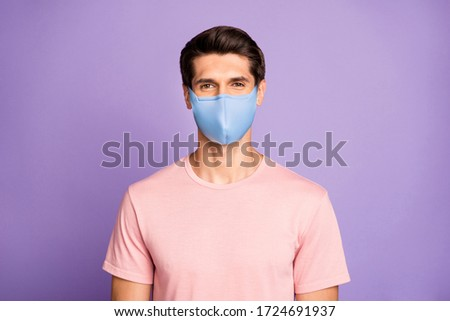 Closeup portrait of attractive glad content brunet guy wear pink t-shirt protection mask on face isolated over violet purple lilac pastel color background Stock photo ©