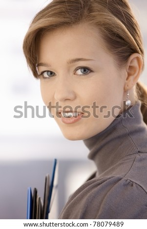Closeup portrait of attractive office worker, holding file folders. Looking at camera, smiling.?