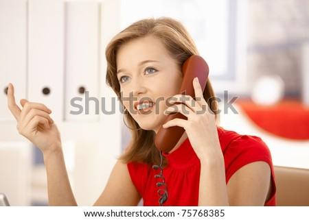 Closeup portrait of attractive office worker, talking on landline phone, gesturing.