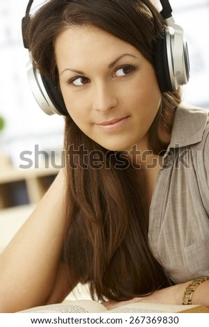 Closeup portrait of attractive young woman with headphones and book, smiling, looking away.