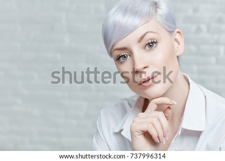 Closeup portrait of attractive young woman with lilac hair, looking at camera, hand on chin.
