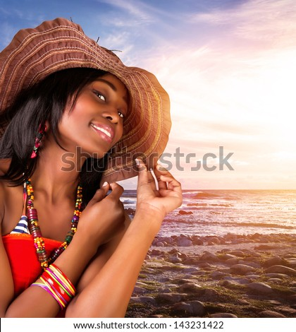 Closeup portrait of beautiful african woman on the beach, sexy model posing on seashore on sunset, wearing stylish hat and fashionable accessories, summer vacation