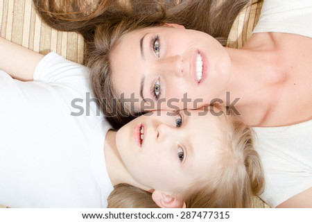 Closeup portrait of beautiful attractive mother and little daughter lying face to face on the sofa